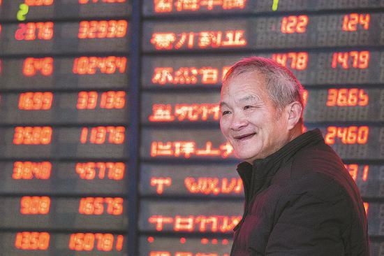 An investor smiles as stocks advance at a securities firm in Nanjing, Jiangsu province, on Monday. (Photo by SU YANG / FOR CHINA DAILY)