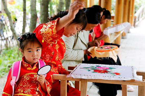 Women in Baoji village of Xihe county, Gansu province, embroider in their spare time to cover some family expenses. (Photo provided to China Daily)