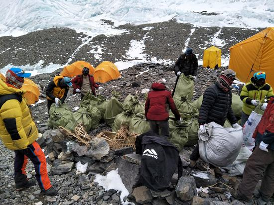 Members of the environmental squad collect trash at base camp on the north face of Qomolangma. (File photo)