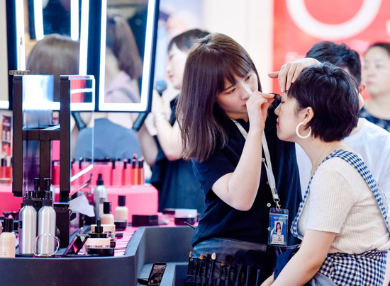 A consumer tries cosmetics at a shopping mall in Beijing. (Photo by Niu Jing/For China Daily)