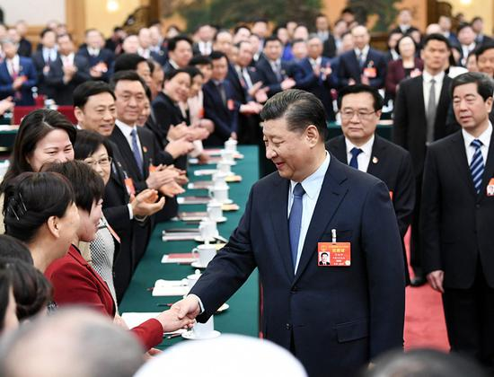 President Xi Jinping extends greetings for International Women's Day to deputies of the National People's Congress during his visit to the Henan delegation in Beijing on Friday. (XIE HUANCHI)