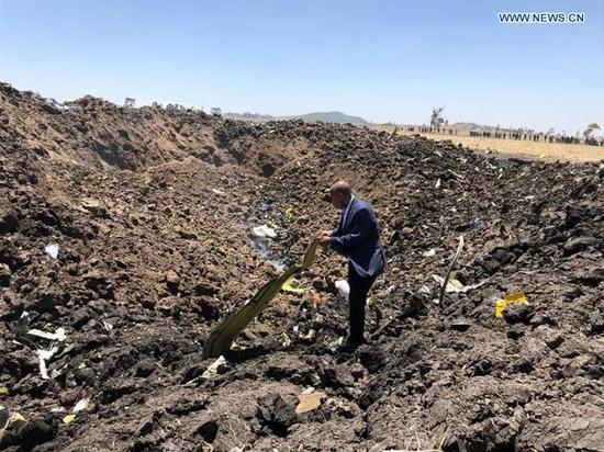 A man checks the wreckage of the airplane of Ethiopian Airlines (ET) which crashed earlier near Bishoftu city, about 45 kms southeast of Addis Ababa, Ethiopia, March 10, 2019. All 149 passengers and eight crew members aboard ET 302, bound for Nairobi, Kenya, are confirmed killed, the Ethiopian Broadcasting Corporation (EBC) said. (Xinhua/Ethiopian Airlines)