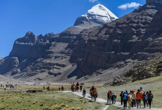 People walk on the foot of the Mount Kangrinboqe in Burang county of Ngari prefecture, Southwest China's Tibet autonomous region, June 24, 2018. (Photo/Xinhua)