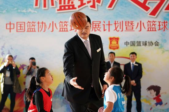 Yao Ming, the retired NBA star and chairman of the Chinese Basketball Association, tosses a jump ball in a children's game at the start of a basketball promotion in Beijing in 2017. (JU HUANZONG/XINHUA)