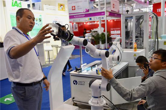 A Han's Laser Tech executive displays a robotic arm at the 20th China High-Tech Fair in Shenzhen, Guangdong province, in November 2018. (Photo provided to China Daily)