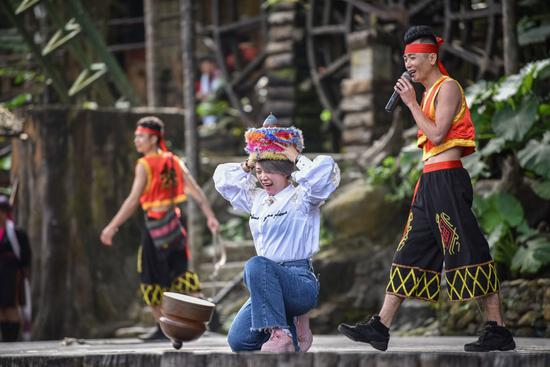 A visitor participates in a performance featuring customs of the Li and Miao ethnic groups in Hainan province in January. (Photo: For China Daily/Yuan Chen)