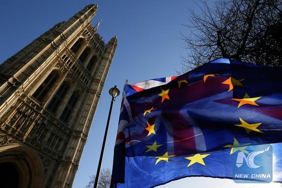 An EU flag is seen in front of a UK flag outside the Houses of Parliament in London, Britain, on Jan. 17, 2019. (Xinhua/Tim Ireland)