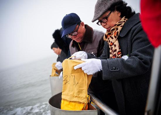 File photo: Citizens scatter the ashes of their deceased relatives in the sea at a sea burial in Tianjin, North China, March 31, 2013. (Photo/Xinhua)