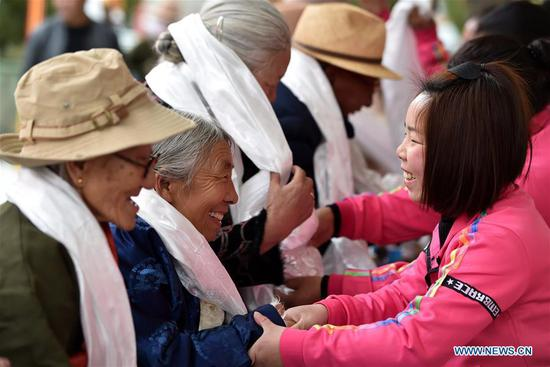 Young people present hada, a white ceremonial silk scarf, to the elderly in an event to celebrate the 60th anniversary of democratic reforms in Tibet, at a community in Lhasa, capital of southwest China's Tibet Autonomous Region, March 23, 2019. (Xinhua/Chogo)