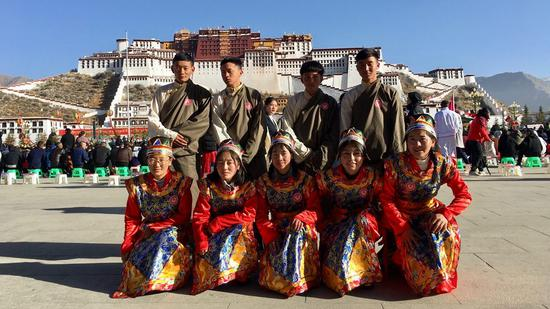 Residents post for a photo in front of the Potala Palace in Lhasa, capital city of southwest China's Tibet Autonomous Region. /CGTN Photo