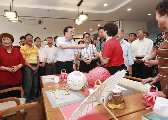 Chinese Premier Li Keqiang, also a member of the Standing Committee of the Political Bureau of the Communist Party of China (CPC) Central Committee, learns about community-based elderly care services at Xin'an community in Haikou, south China's Hainan Province, March 27, 2019. (Xinhua/Pang Xinglei)