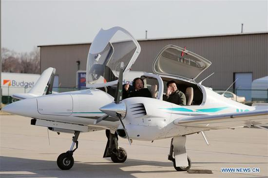 Zhang Bo (L, Front) and his co-pilot gesture before taking off at an airport in Chicago, the United States, on April 2, 2019. The 57-year-old Chinese man Zhang Bo kicked off his second flight around the world on Tuesday in a Diamond DA42 aircraft from Chicago. (Xinhua/Wang Ping)