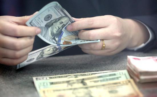 A bank staff member counts U.S. dollar banknotes at a bank in Tancheng County of Linyi City, east China's Shandong Province. (Xinhua/Zhang Chunlei)