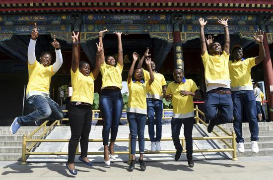 File photo: African students, who work as volunteers at Yuanmingyuan, or the Old Summer Palace, jump in unison for a group photo in Beijing.  (Photo/Xinhua)