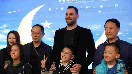Goran Marinovic (C) poses with children and school staff at a ceremony during which he donates 100,000 yuan to Suzhou Ren'ai School to help its autistic children. /CGTN