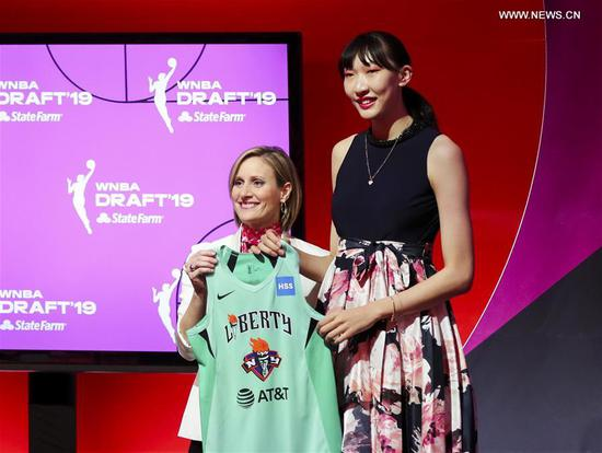 Han Xu (R) of China poses for a photo with WNBA COO Christy Hedgpeth after being selected by the New York Liberty in the second round of the WNBA women's basketball draft in New York, the United States, April 10, 2019. (Xinhua/Wang Ying)