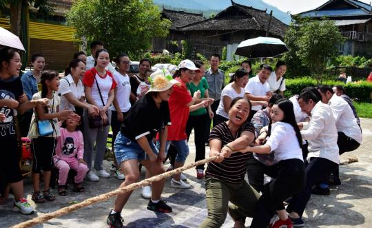 Members of staff join in a tug-of-war in Congjiang county, Guizhou province. (Luo Jinglai / For China Daily)
