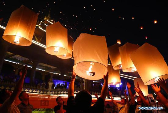 People fly Kongming lanterns by Lancang River in Yunnan