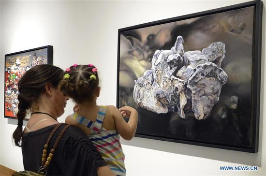 Visitors admire the work of a Chinese artist on a themed exhibition held in Havana, Cuba, April 13, 2019. (Photo/Xinhua)