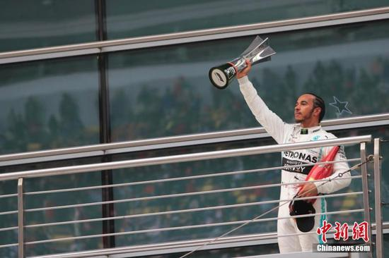 Mercedes driver Lewis Hamilton of Britain celebrates on the podium after winning the Chinese Formula One Grand Prix at the Shanghai International Circuit in Shanghai, China, April 14, 2019. (Photo: China News Service/Yin Liqun)