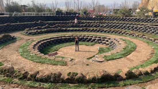 Columbia designer Alexandra Posada stands in the middle of a potato farm inspired by ancient Inca agricultural terraces. (Photo/CGTN)
