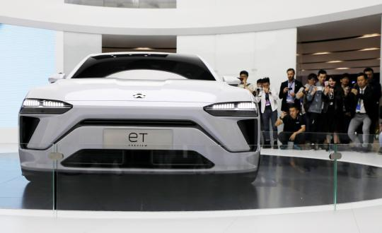 Visitors take snapshots of an eT electric vehicle during a recent auto exhibition in Shanghai. (Photo by Fang Zhe/Xinhua)