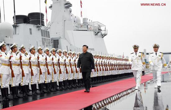 Chinese President and Central Military Commission Chairman Xi Jinping inspects the honor guards of the Chinese People's Liberation Army (PLA) Navy before boarding the destroyer Xining at a pier in Qingdao, east China's Shandong Province, on April 23, 2019. (Xinhua/Li Gang)