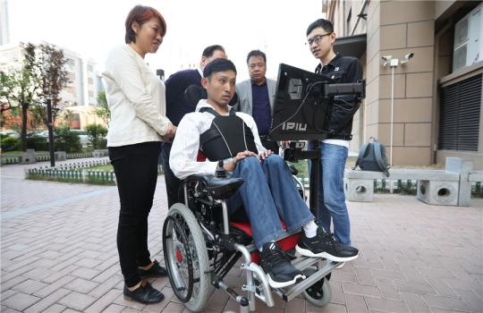 Zhang Wei operates the wheelchair at a residential community in Xi'an, Shaanxi province, April 17, 2019. (Photo by Chen Feibo/For chinadaily.com.cn)