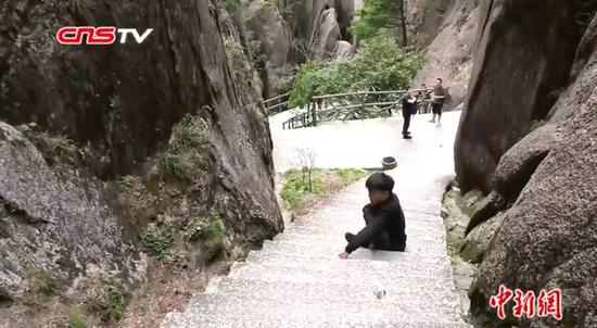 Disabled Li Chuangye climbs Mount Huangshan with his hands in Anhui Province. (Photo/Screenshot on CNSTV)