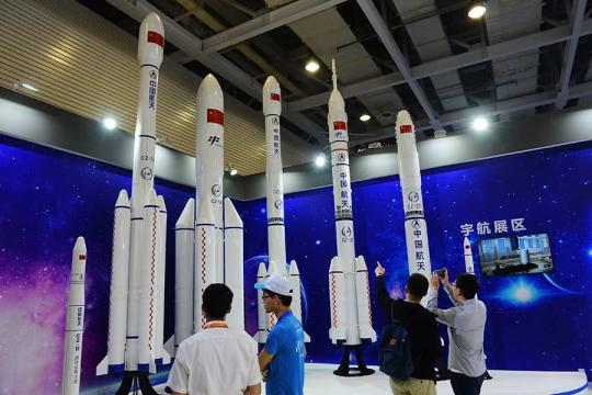 Visitors examine models of various types of Long March rockets in Changsha, Hunan Province, on Tuesday. The exhibit highlights China's achievements in astronautics. (Photo by Xu Xing/for China Daily)