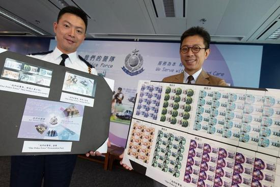 Hong Kong Post's Senior Manager (Philatelic Marketing) Nelvin Lee (R) and Chief Drill and Musketry Inspector Lo Yee-chung pose with