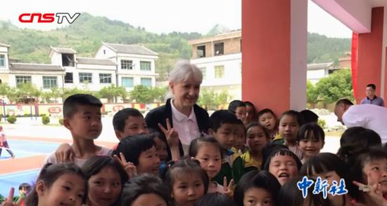 German sinologist and writer Petra Haering-Kuan  poses for a group photo with children from Pingtang, Guizhou Province. (Photo/Screenshot on CNSTV)