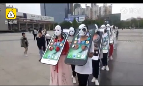 Students' heads and arms are in a pillory in the shape of mobile phones. (Screenshot photo/Pear Video)