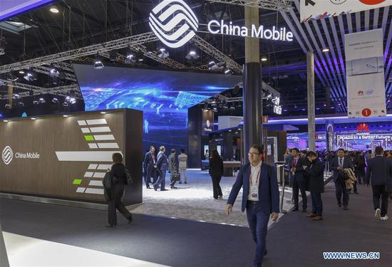 People walk past China Mobile's booth during the first day of the 2018 Mobile World Congress (MWC) in Barcelona, Spain, on Feb. 26, 2018. [Photo/Xinhua]