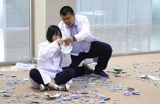 Two staff members from Yuanmingyuan Ruins Park compare broken porcelain pieces on Friday to prepare for restoration.  (Photo by ZOU HONG/CHINA DAILY)