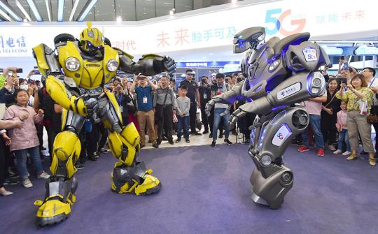 Two 5G robots are displayed at China Telecom's exhibition area during the Fourth Silk Road International Exposition in Xi'an, capital of Shaanxi province, on May 12. (Photo by YUAN JINGZHI/FOR CHINA DAILY)