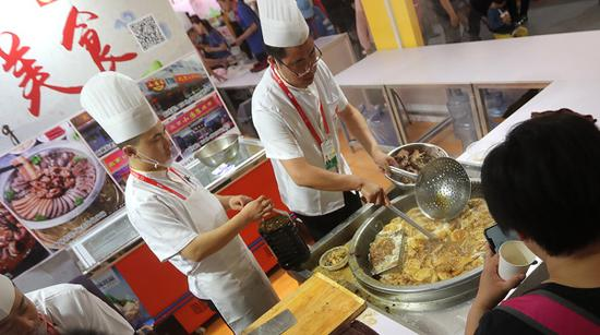 A tourist tastes a traditional Beijing snack, luzhu huoshao-pig intestines and lungs cooked together with bean curd-at the Asian Food Festival in Beijing on Thursday. (Photo provided to China Daily)