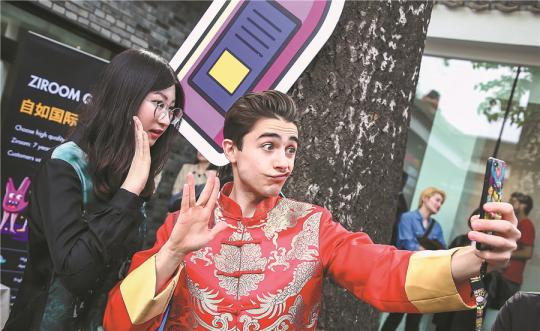 A foreigner in traditional Chinese menswear called Tangzhuang or Tang suit, takes a selfie with a visitor at the Bazinga Hutong Festival, a community event organized by Ziroom to help more foreigners better understand, and adapt to living in, China. (Photo provided to China Daily)