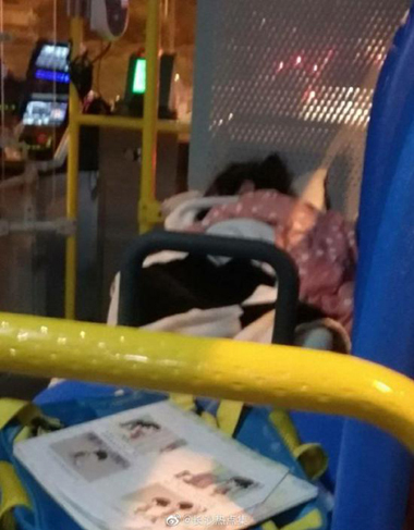 A little girl, about four to five years old, was seen lying asleep on a bus seat with a quilt, pillow and books, on May 21, 2019. (Photo from Weibo)