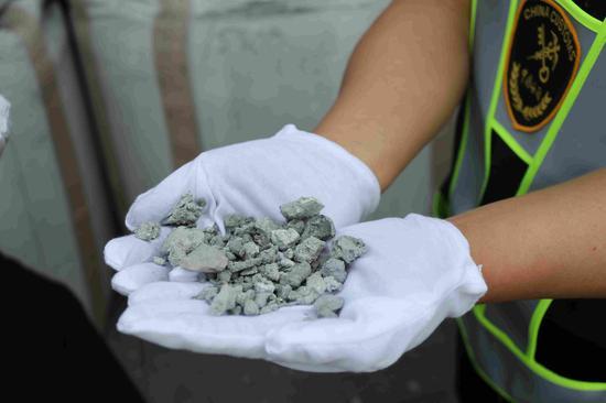 Custom officials check smuggled aluminum dross. /Photo via Dalian Customs