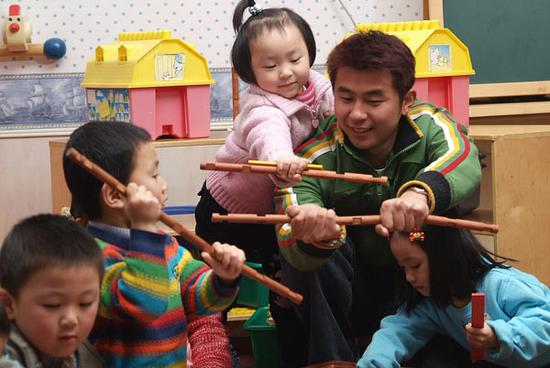 A preschool teacher plays with children in his classroom in Shanghai. (Photo provided to China Daily)