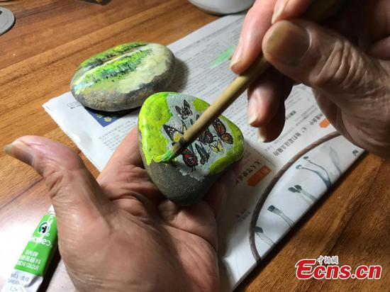Old man creates paintings on stones