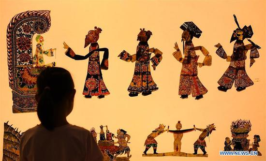 A kid views shadow puppets at an intangible cultural heritage fair on cultural and natural heritage day in Guangzhou, capital of south China's Guangdong Province, June 8, 2019. More than 3,200 activities have been scheduled across China to celebrate this year's cultural and natural heritage day, which falls on June 8.(Xinhua/Deng Hua)