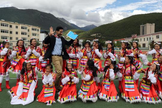 Rupak Sapkota from Nepal interacts with primary students in Nyingchi, Tibet autonomous region, on Monday. He was one of the foreign journalists invited by the State Council Information Office and the government of the Tibet autonomous region to witness the development of the local economy and ecological protection in the area. (WANG JING/CHINA DAILY)