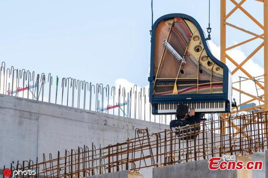 Pianist gives concert from vertical piano hanging from construction crane