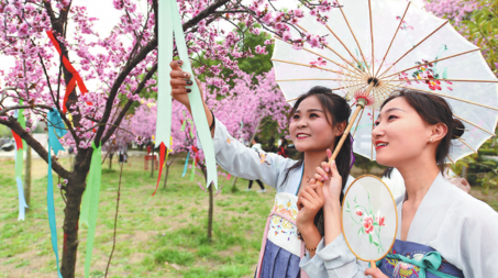 Women in traditional hanfu attire tie a ribbon to a tree in Fuyang, Anhui province. (Photo by WANG BIAO/FOR CHINA DAILY)