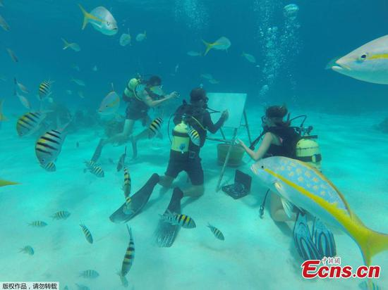 Cuban artist sketches under the sea among fish reefs and corals