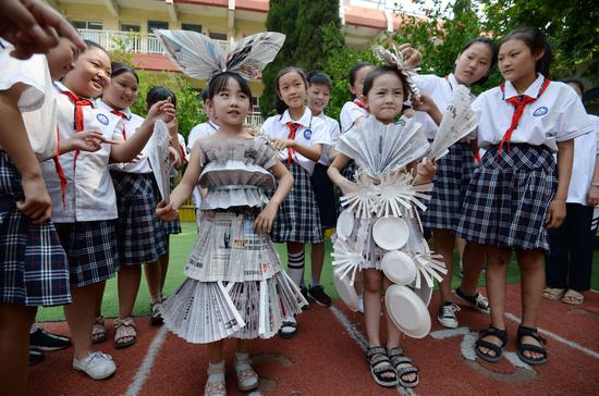 Students display costumes made from recycled newspapers and paper plates in Handan, Hebei province, on Tuesday, ahead of the National Low Carbon Day on Wednesday. (HAO QUNYING/FOR CHINA DAILY)