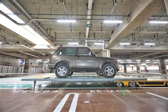 A car is hoisted up into a parking space at the Beijing Capital International Airport. (Photo/Beijing News)