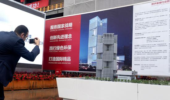 A guest to the New Development Bank's structure ceiling ceremony, which was held on Wednesday in Shanghai, takes a snapshot of the building's diagram. (Photo by Gao Erqiang/China Daily)